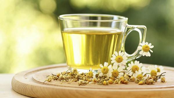 Чашка с чаем и цветки ромашки