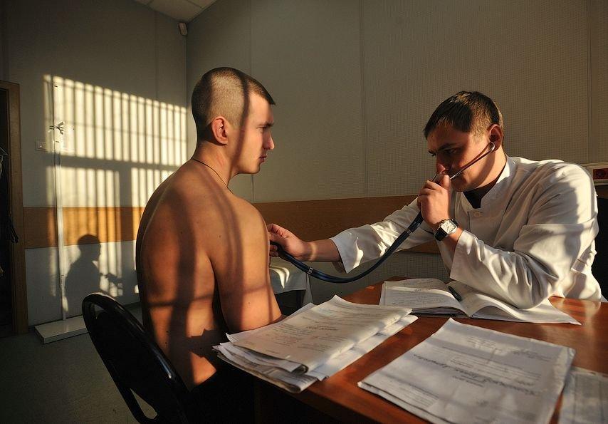 Врач внимательно проверяет мужчину перед отдачей военного долга