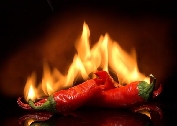 Красный перец на фоне огня