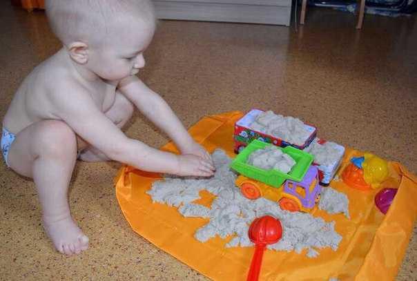 Малыш в 17 месяцев играет с песком дома