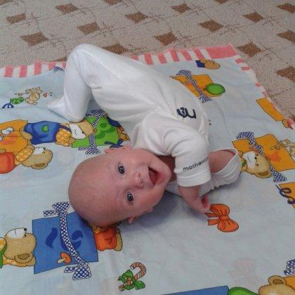 трехмесячный ребенок пытается переворачиваться