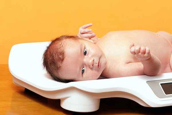 взвешивание малыша при осмотре педиатром